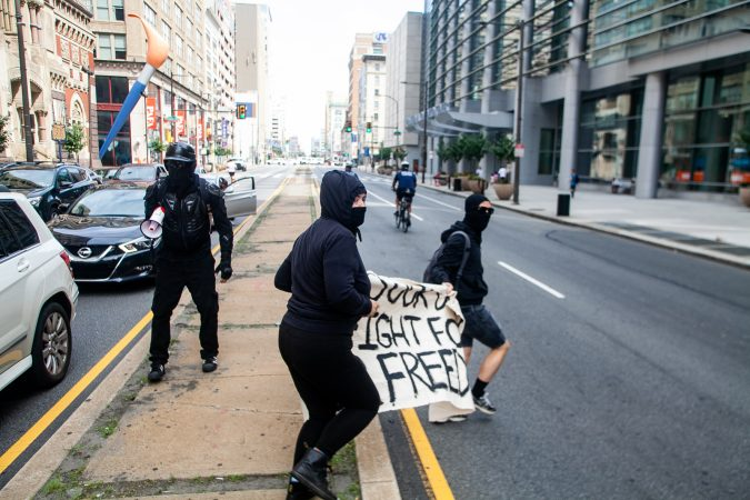 Antifa protestors ran up Broad Street after evading a police blockade in an attempt to intercept a Blue Lives Matter march. (Brad Larrison for WHYY)