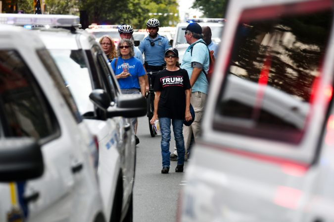 Participants in the Blue Lives Matter march watch from behind police vehicles as a group of counter protestors blocks the path of the march, at Broad and Arch Streets, on  Saturday. (Bastiaan Slabbers for WHYY)