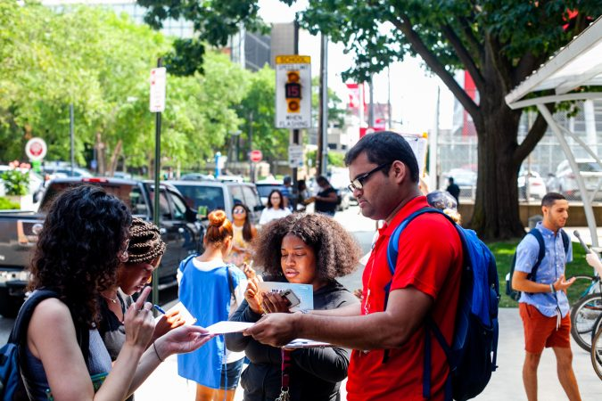 Razin Karu, a Temple University senior and fellow with NextGen, passes out surveys to fellow students that could be redeemed for free ice cream. (Brad Larrison for WHYY)
