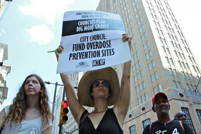 Protesters from ACT UP and Sol Collective gather outside City Hall to demand funding for overdose prevention sites in Philadelphia. (Emma Lee/WHYY)