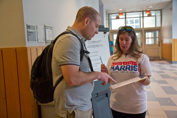 Steph Herron signs Wilmington resident Sean Vernon up to volunteer on Kerri Harris' election campaign. (Kimberly Paynter/WHYY)