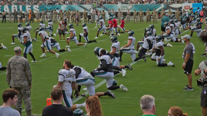 The Philadelphia Eagles strech before their first open practice Sunday evening. (Kimberly Paynter/WHYY)