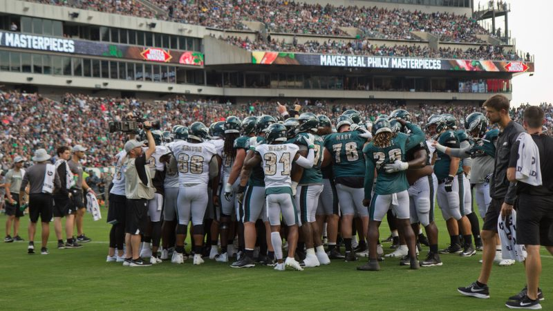 The Philadelphia Eagles huddle at their first open practice of the season Sunday evening. (Kimberly Paynter/WHYY)