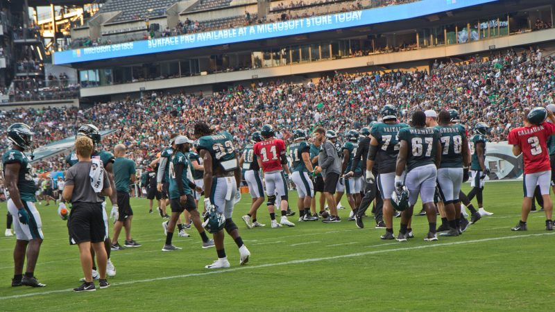 The Philadelphia Eagles huddle during the team's first open practice Sunday evening. (Kimberly Paynter/WHYY)