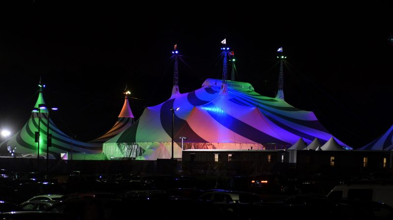 Cirque's Grand Chapiteau is seen lit up in vibrant colors reflecting off the white surface, as it is located next to the Greater Philadelphia Expo Center, in Oaks, Pa. To achieve a higher level of sustainability the Toronto-based Cirque changed its iconic big tops from blue and yellow to white and grey. (Bastiaan Slabbers for WHYY)