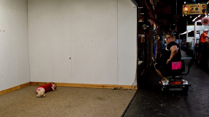 A child takes a break on the floor of an empty stall at Zern's Farmers Market in Gilbertsville, Pa., on Aug. 24, 2018. (Bastiaan Slabbers for WHYY)