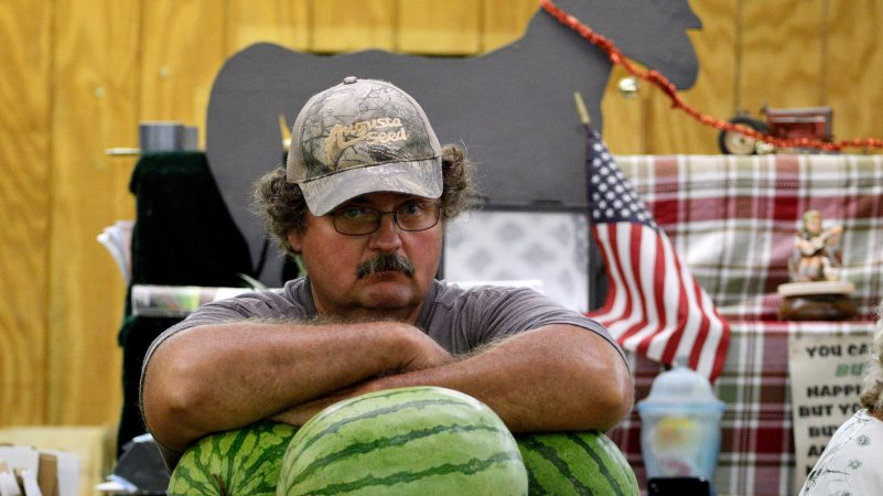 A vendor rests his arms on the melons at a produce stand at Zern's Farmers Market in Gilbertsville, Pa. (Bastiaan Slabbers for WHYY)
