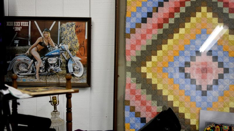 A signed copy of Miss Bike Week 1994 shares a wall with a framed quilt in a booth at Zern's Farmers Market in Gilbertsville, Pa. (Bastiaan Slabbers for WHYY)