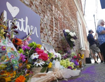 A memorial to Heather Heyer — who was killed at last year's Charlottesville rally by a driver facing murder and hate crime charges — stands at the site of her death. Heyer's mother, Susan Bro, is in the background. (Steve Helber/AP)