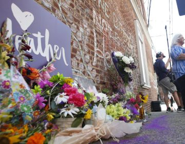A memorial to Heather Heyer — who was killed at a Charlottesville rally by a driver facing murder and hate crime charges — stands at the site of her death. Heyer's mother, Susan Bro, is in the background. (Steve Helber/AP)