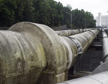 Transfer pipes carry liquified natural gas to and from a holding tank, seen in background, at Dominion Energy's Cove Point LNG Terminal in Lusby, Md., Thursday, June 12, 2014. Federal regulators concluded that Dominion Energy's proposal to export liquefied natural gas from its Cove Point terminal on the Chesapeake Bay in Maryland would pose