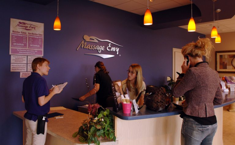 Receptionists check in a customer at a Massage Envy in this file photo (L.G. Patterson/AP Photo)