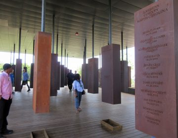 This April 28, 2018 photo shows visitors looking at markers bearing the names of lynching victims at the National Memorial for Peace and Justice in Montgomery, Ala. The memorial includes some 800 markers, one for each county in the U.S. where lynchings took place, documenting the killings of more than 4,400 individuals between 1877 and 1950. (AP Photo/Beth J. Harpaz)