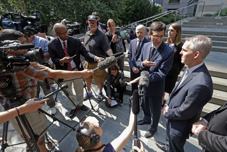 Washington Attorney General Bob Ferguson, third right, speaks with media members following a hearing where a federal judge issued a temporary restraining order to stop the release of blueprints to make untraceable and undetectable 3D-printed plastic guns, Tuesday, July 31, 2018, in Seattle. Ferguson was among eight Democratic attorneys general who filed a lawsuit Monday seeking to block the federal government's settlement with the company that makes the plans available online. They also sought a restraining order, arguing the 3D guns would be a safety risk. (AP Photo/Elaine Thompson)