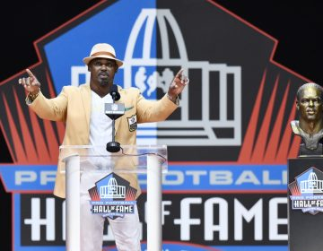 Former NFL player Brian Dawkins delivers a speech beside during an induction ceremony at the Pro Football Hall of Fame, Saturday, Aug. 4, 2018, in Canton, Ohio. (AP Photo/David Richard)