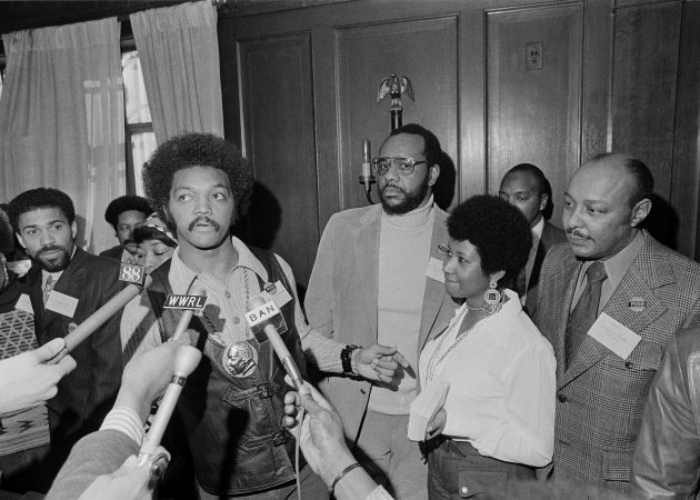Rev. Jesse Jackson speaks to reporters at the Operation PUSH Soul Picnic at the 142nd Street Armory in New York, March 26, 1972. Left to right are: Betty Shabazz, behind Jackson, widow of Malcolm X; Jackson; Tom Todd, vice president of PUSH; Aretha Franklin and Louis Stokes. PUSH stands for People United to Save Humanity. (AP Photo/Jim Wells)