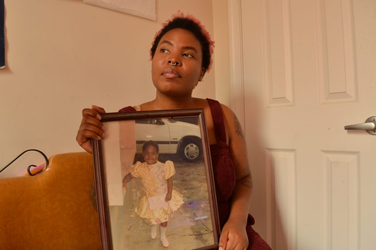 Adesola Ogunleye holds a picture of herself as a young child. She says childhood abuse has played into the anxiety she deals with now, as an adult. (Liz Tung/WHYY)
