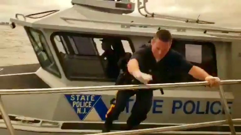 A state trooper prepares to jump onto a moving sightseeing boat off Atlantic County Monday afternoon to render assistance to an unconscious man. (Image taken from a video courtesy of Kevin Gilbert)