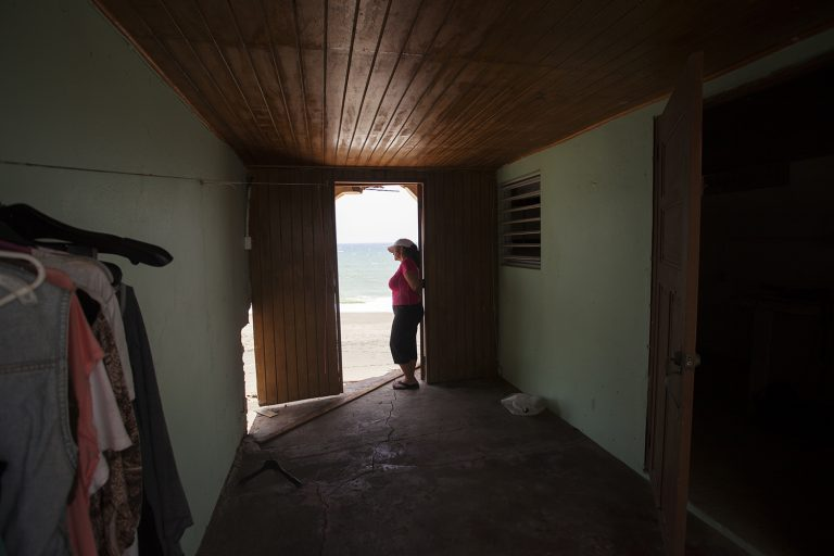Rosa Elena Mastache Dominguez looks out at the beach through a door that once led to the back of her family home. Hurricane Maria shrunk the beach behind her home, then another storm brought waves that destroyed the structure. (Irina Zhorov/WHYY)