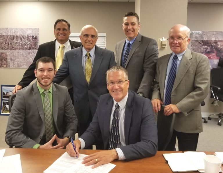 Contract signing by ACEA Executive Director Lauren H. Moore Jr. with USDA loan specialist Joseph Henry (seated to left) and (standing, from left) Max Slusher, ACEA business development director; Michael Zumpino, Triad Associates chairman and CEO; Noel McGuire, ACEA business aviation representative; and Steve Kehs, Triad Associates vice president. (Provided)