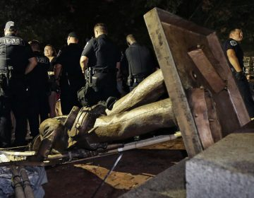 Police stand guard after the Confederate statue known as