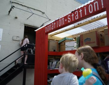 Teachers visit the Baltimore Teacher Supply Swap, perusing racks of educational posters and tubs of rulers. (Eslah Attar/NPR)
