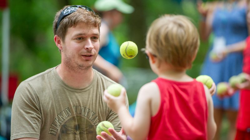 Daryl Faust teaches his son to juggle in Dulcimer Grove. Faust has been attending the folk festival since he was 10 months old. (Jonathan Wilson for WHYY)