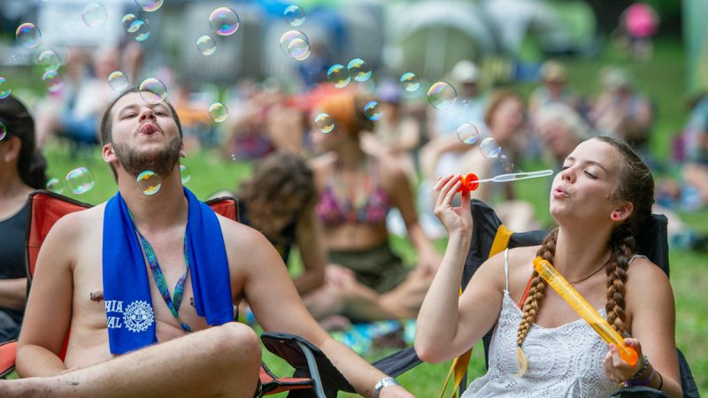 Cyndey Rader blows bubbles while friend Harrison Mask attempts to pop them in front of the Camp Stage. (Jonathan Wilson for WHYY)