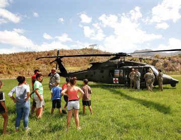 In the mountain town of Juyaya, Puerto Rico, last October, children watched as U.S. Army helicopters brought a team of physicians to assess the medical needs of the local hospital and residents. Going forward, health economists say, the U.S. territory will need continued federal help to deal with its overwhelming Medicaid expenses. (Carolyn Cole/Los Angeles Times via Getty Images)