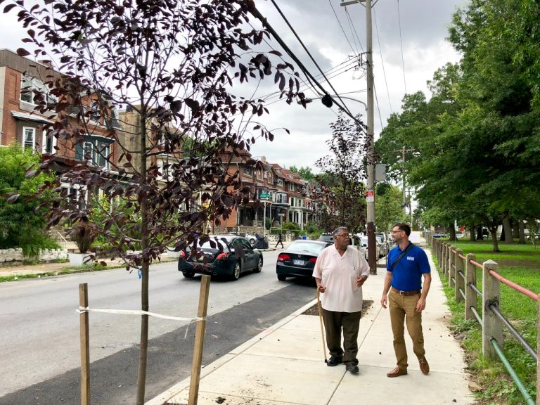 Gregorio Pac Cojulun (left), and Dan Schupsky, an outreach specialist, stroll along one of the new sidewalks. (Meir Rinde/PlanPhilly)