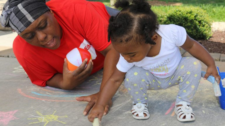 Marletha Muhammad helps her daughter, Khanila, spell her name with chalk at a June playgroup meeting in Rocky Mount, North Carolina The purpose of the meetings is to encourage healthy interactions between parents and their young children. (Liz Bell/The Hechinger Report)