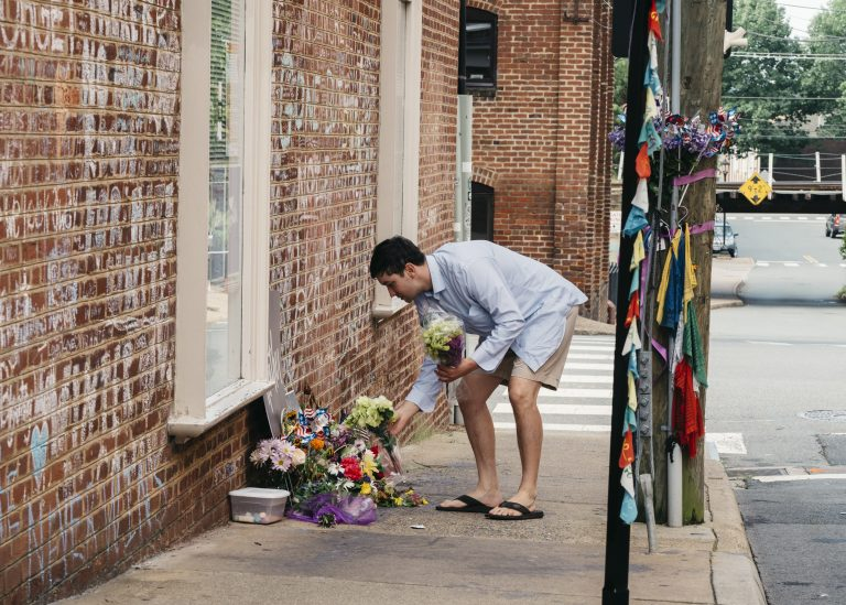 Peter Reijmers, 29, of Charlottesville, lays flowers at a memorial on 4th Street SE where Heather Heyer was killed last August. (Justin T. Gellerson/NPR)