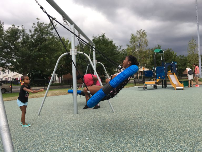 Youngsters try out the new swings at Lanier Playground during a tour in advance of its official reopening.   Malcolm Burnley/PlanPhilly)