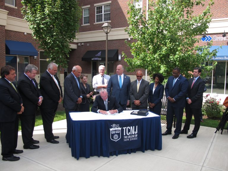 Governor Phil Murphy signs the new law at the College of New Jersey (Phil Gregory/WHYY News)