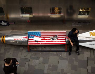 A man sits on a promotional gimmick in the form of a bomb and the U.S. flag outside a U.S. apparel shop at a shopping mall in Beijing. China says it's girded for a trade war with the U.S. and can give as good as it gets, but behind the official bravado lies a deep unease over trade friction with Washington. (AP Photo/Mark Schiefelbein)