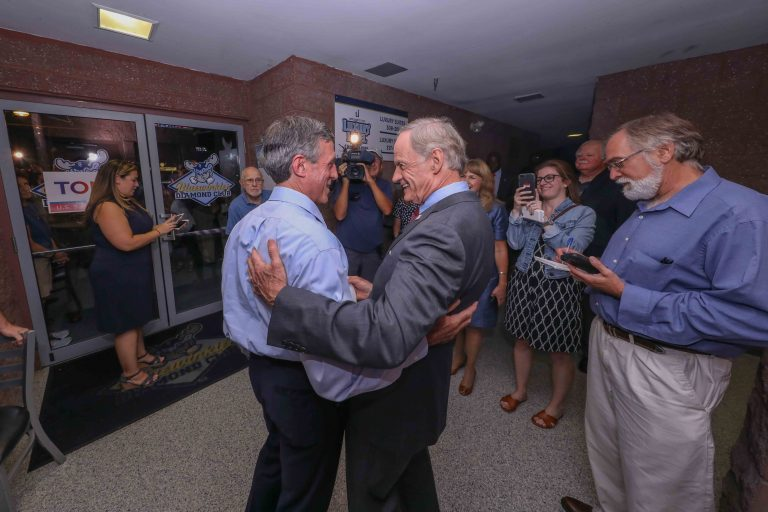 United States Senator Tom Carper (right) greets Governor John Carney during a Primary Election gathering Thursday, Sept. 06, 2018, at Frawley Stadium in Wilmington, Delaware. (Saquan Stimpson/for WHYY)