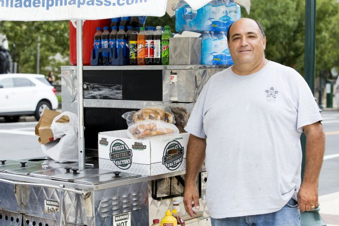 Dominic Mazza, 51, poses with his hot dog stand, Mazza Brothers Hot Dogs, outside of the Franklin Institute on Saturday. A licensed vendor, Mazza says that the vendors selling bottled water without permits