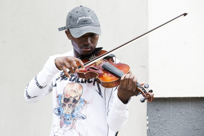 Rickey Turner, 21, plays the violin for passers-by outside of the Made in America festival. (Rachel Wisniewski for WHYY)