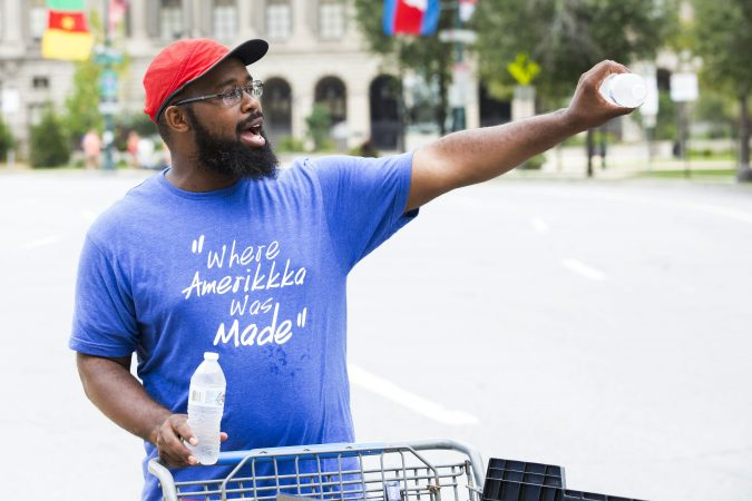 Saadiq Garner, 29, sells water bottles, Gatorade, and rain ponchos outside the Made in America festival Saturday. A car salesman for 13 years, Garner hoped to make some extra cash. (Rachel Wisniewski for WHYY)