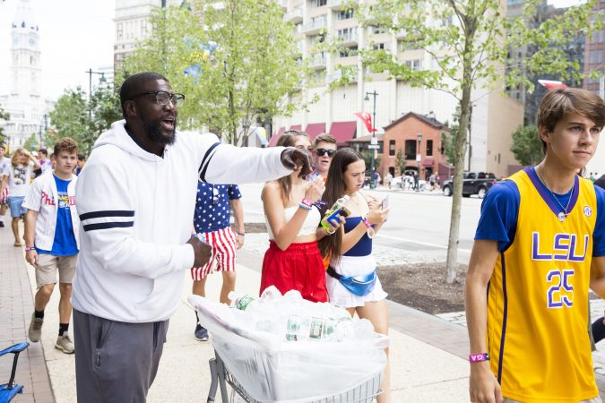 Warren Kale (left) attempts to sell water outside the Made in America festival Saturday. Vending water bottles is currently Kale's primary source of income.  (Rachel Wisniewski for WHYY)