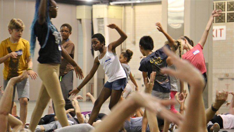 Members of the children's troupe wade through a sea of waving arms during a rehearsal for