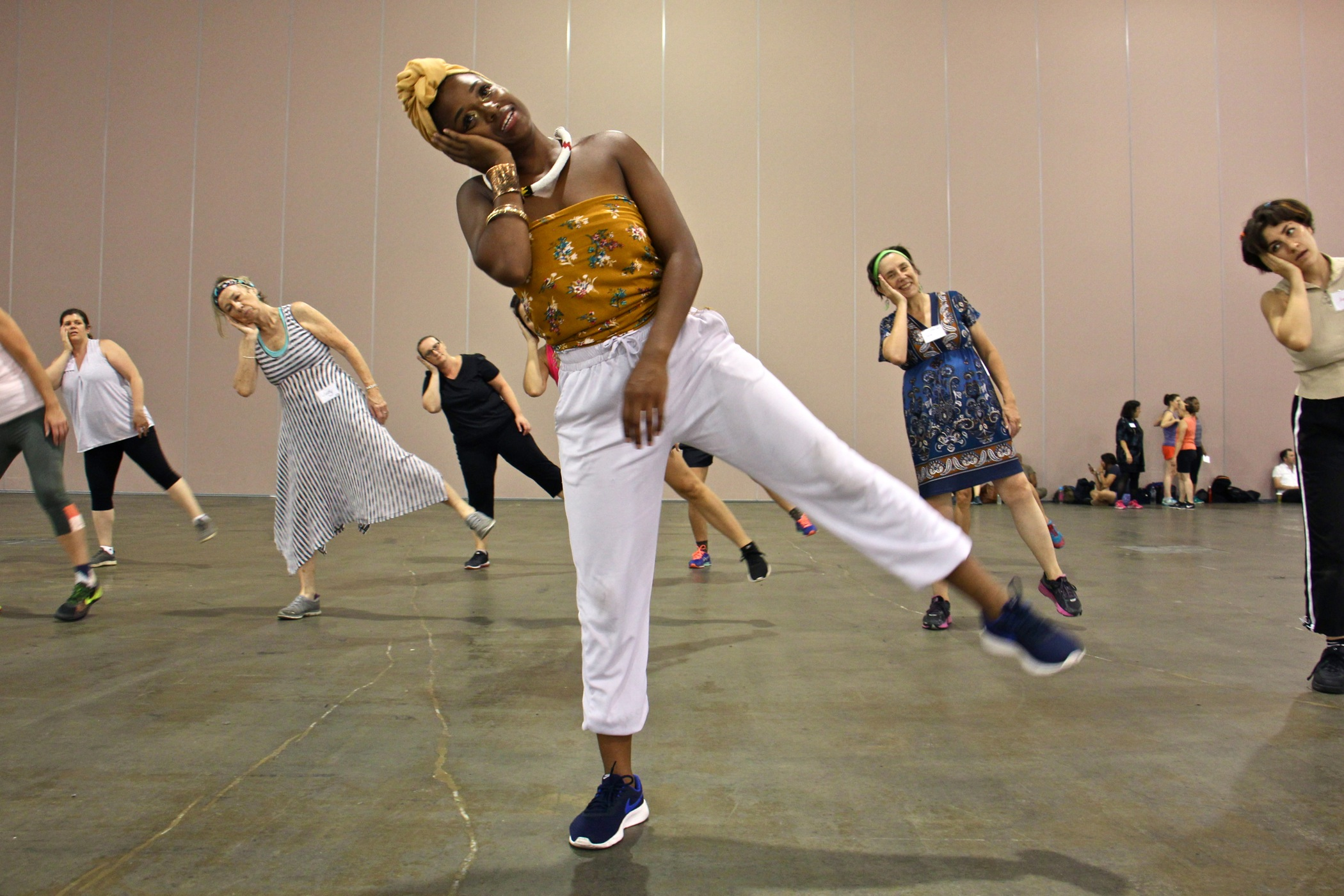 """Rehearsal assistant Sanchel Brown leads a group warmup during rehearsal for """"Le Super Grand Continental,"""" which will be performed by 175 volunteer dancers at the steps of the Philadelphia Art Museum during the Fringe Festival."""