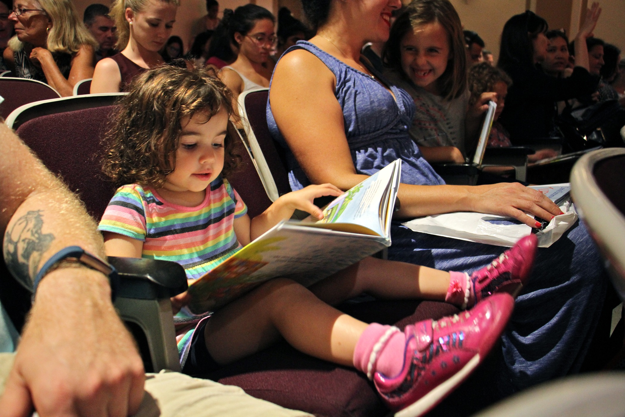 "Estie Johnson, 2, of Philadelphia browses Sonia Sotomayor's new book, ""Turning Pages,"" while waiting for the arrival of the Supreme Court Justice at the Free Public Library Central branch with her parents and two sisters."