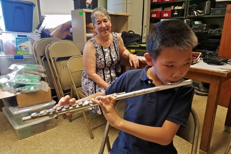 Leo Zhang, a student at Mayfair Elementary, will learn to play on a flute repaired through the Broken Orchestra program. Behind him is Tobie Hoffman, who played the flute in the