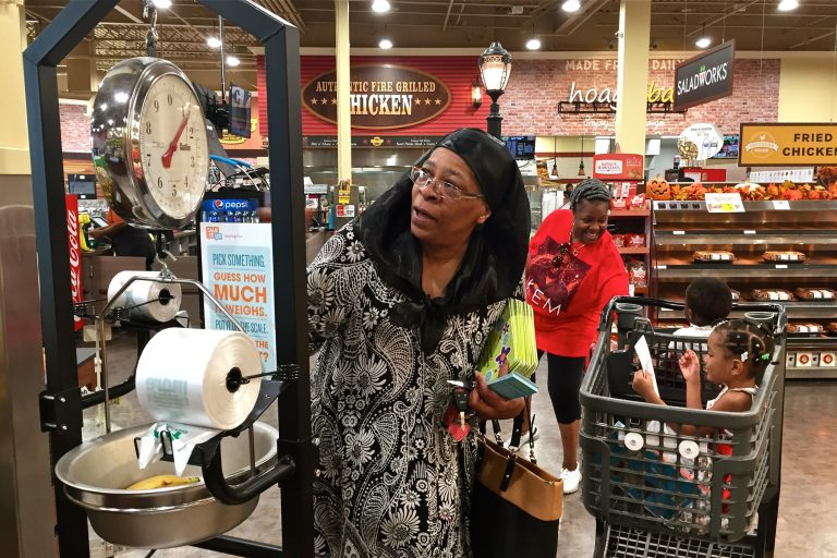 April Ellis weighs some bananas at the Island Avenue Shoprite in Southwest Philadelphia while shopping with her grandchildren,  Kalanni and Shareef. (Avi Wolfman-Arent/WHYY)