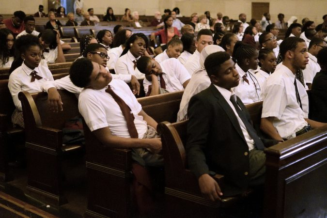 "Students attempt to listen to the speakers as the temperature in the chapel rises, during the ""Opening the Gates"" forum, on Tuesday at Girard College. (Bastiaan Slabbers for WHYY)"