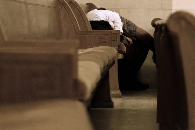 In the back of the chapel, a student finds a good place to rest in the pews. (Bastiaan Slabbers for WHYY)