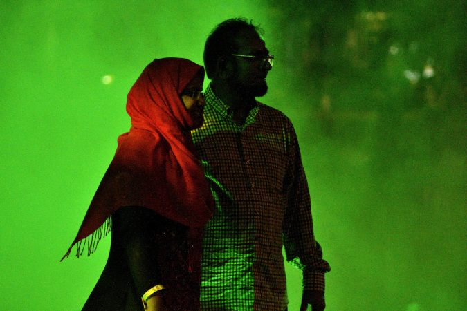 The red headscarf of a visitor lights up in contrast to the green mist during the public unveiling of