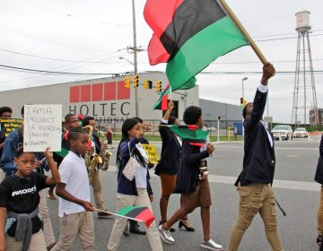 Camden students march outside Holtec International, protesting remarks made by the company's CEO Krishna Singh that residents of the city don't know how to work. The company received $260 million in tax breaks to build its manufacturing plant in Camden. (Emma Lee/WHYY)