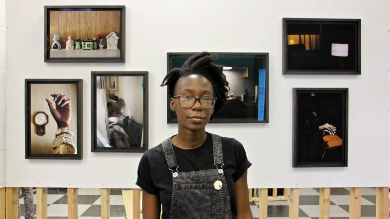 Danielle Morris stands before a collection of photographs she calls